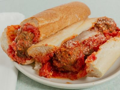 Meatballs, parmesan cheese, and marinara sauce in a hero roll.